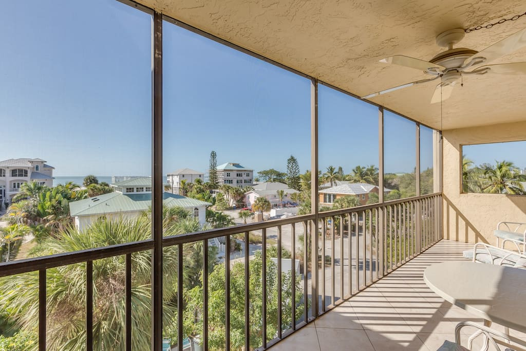 A ceiling fan keeps things cool on the screened lanai with Gulf views
