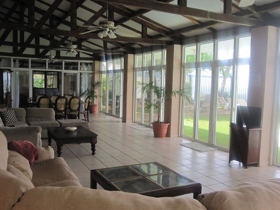 Glassed living area with 2 sectional sofa & 2 eating areas facing pool & ocean