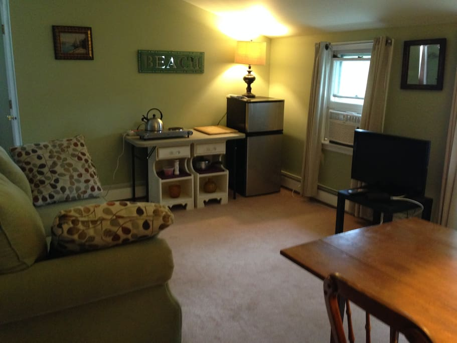 The living area:  small refrigerator, desktop stove, Cable TV,  window air conditioner, closets, dresser, dining table, glassware, and eating utensils.  Refrigerator stocked with bottled water.  There is also an extra queen bed in this room