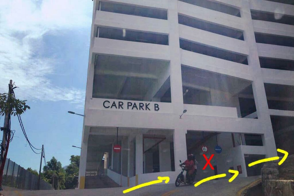 DO NOT enter here (marked 'X'). Drive all the way uphill & go around the 2 blocks of condo.