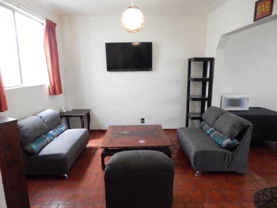 Sala con TV y radio vintage. / Living room with TV and vintage radio.