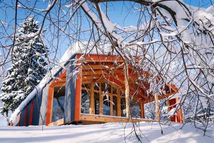 Современный зимний дом с камином и видом на пруд