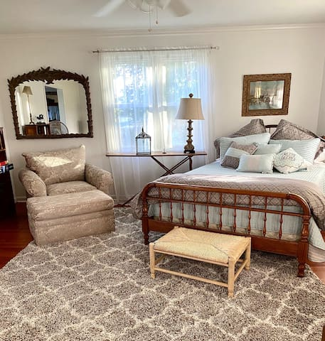 Bedroom with a queen bed and a big chair that is perfect for reading and relaxing.