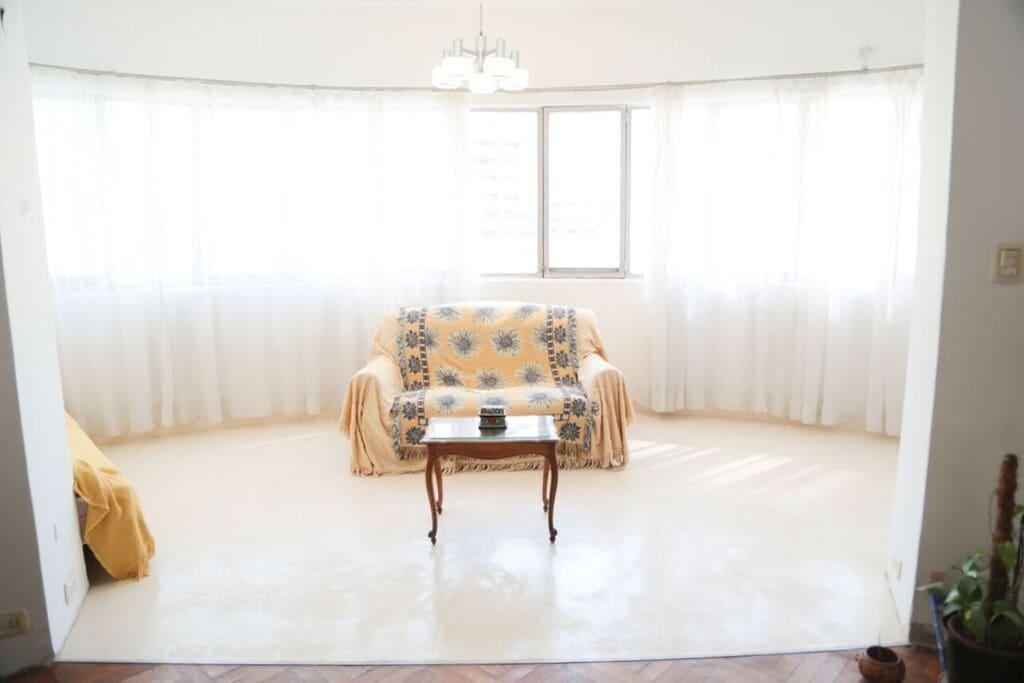 Vista del ventanal desde el piso de madera del living, a la izquierda la cama de una plaza.