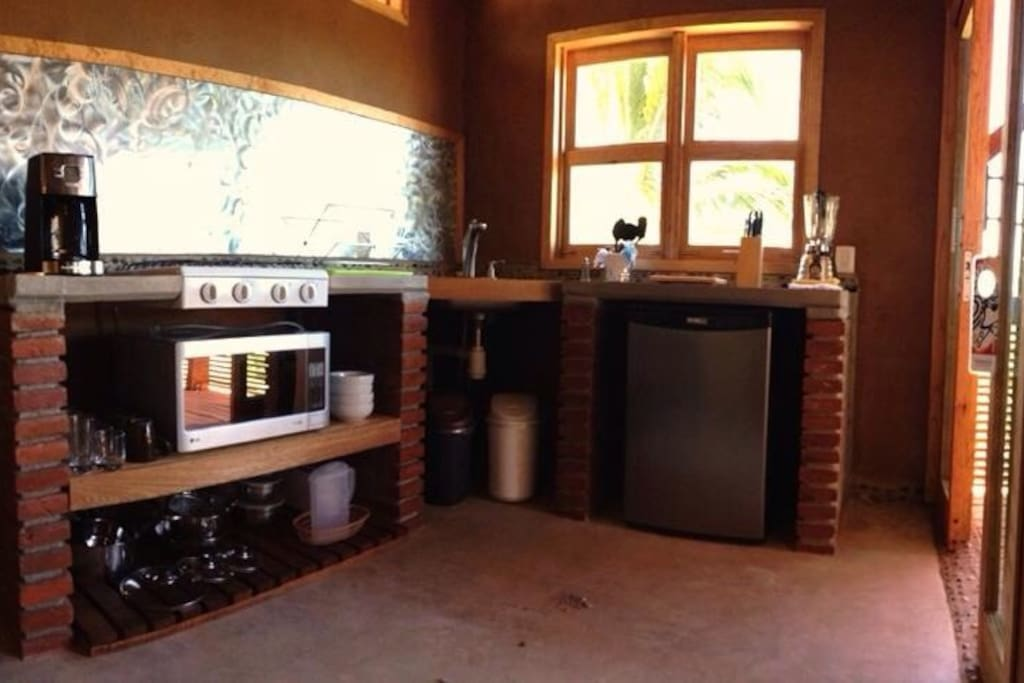 Kitchenette with fridge, coffee machine, blender, microwave, gas stove and more.