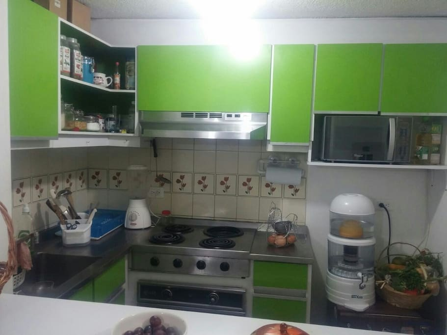 cocina con estufa eléctrica nevera a pequeña horno microondas purificador de agua vajilla y utensilios