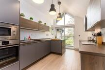 """Modern kitchen with breakfast bar seating 2  ⭐Our guests say: """"Light, airy, and spacious""""⭐"""