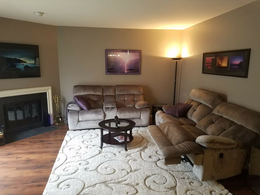 Living room with fireplace and sliders to balcony and gorgeous  new laminate, new paint and new power recliners !