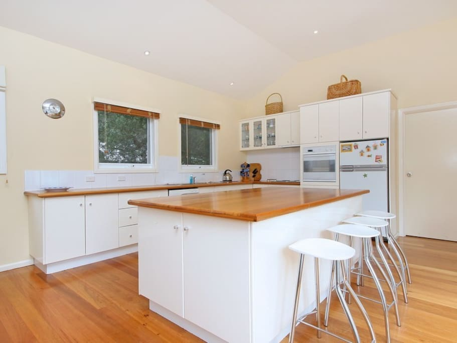 Large open plan kitchen with dishwasher, oven stove and microwave.