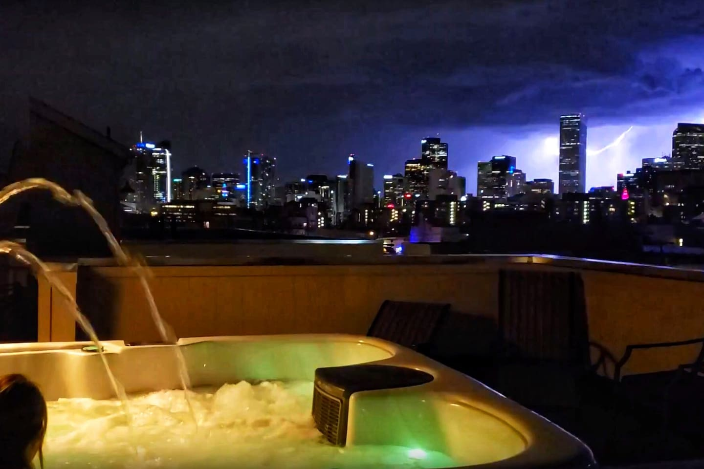 Hot tub on the roof with lightning storm behind Denver skyline!