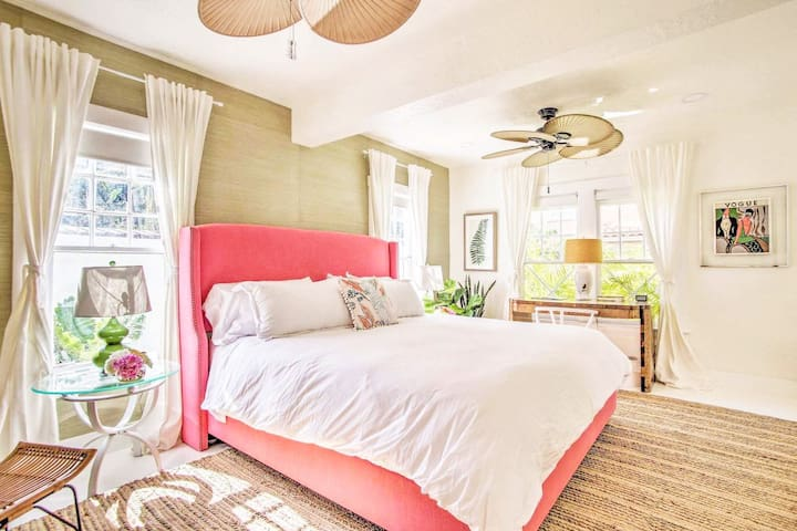 The bedroom with a coral headboard and light green grasscloth wallpaper features a king-sized bed.