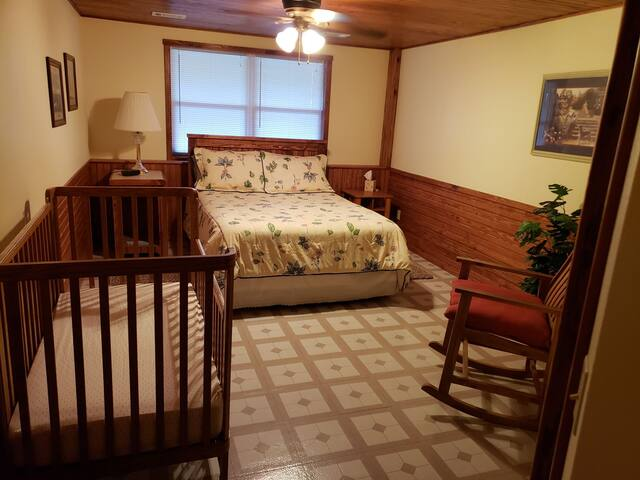 Queen sized bed in the Master bedroom.  Baby bed and a comfortable rocking chair provided for the young families