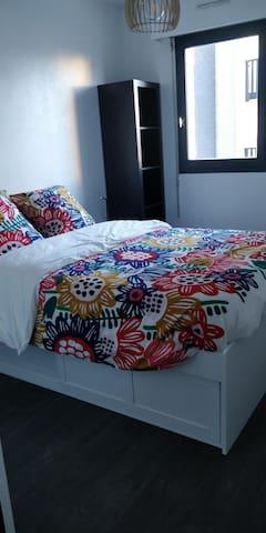 Chambre avec lit 140x190 rangements sous le lit et deux colonnes des deux côtés  Tablettes de chevet avec lampe et prise pour tel portable