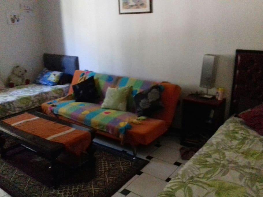 une chambre avec deux lit et un fauteuil lit avec veux aussi sur le jardin