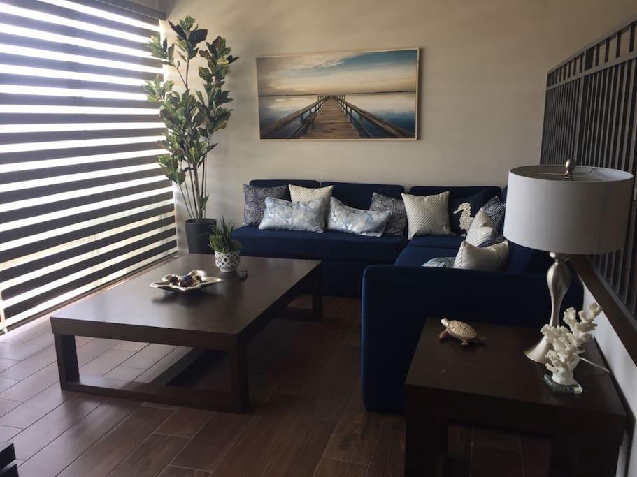 Sala con un estilo contemporáneo el cual el sofá se convierte en cama para 2 personas