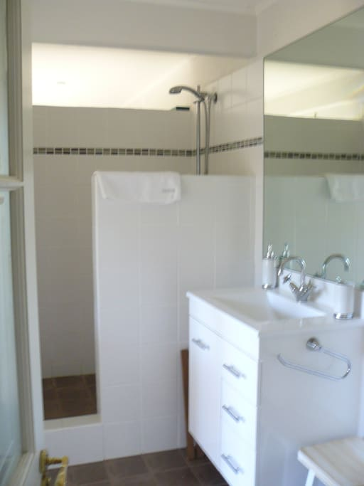 Clean and light bathroom with large mirror.