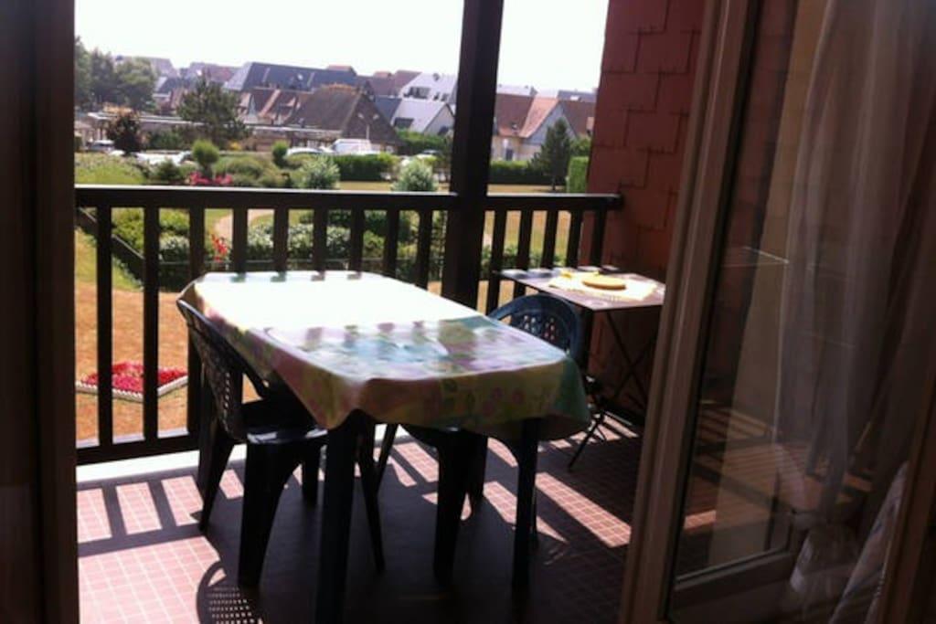 Loggia ensoleillée avec vue sur jardin. Table de jardin et ses 6 chaises