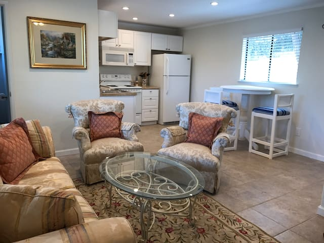 Spacious living room with kitchen, eating nook, and desk area