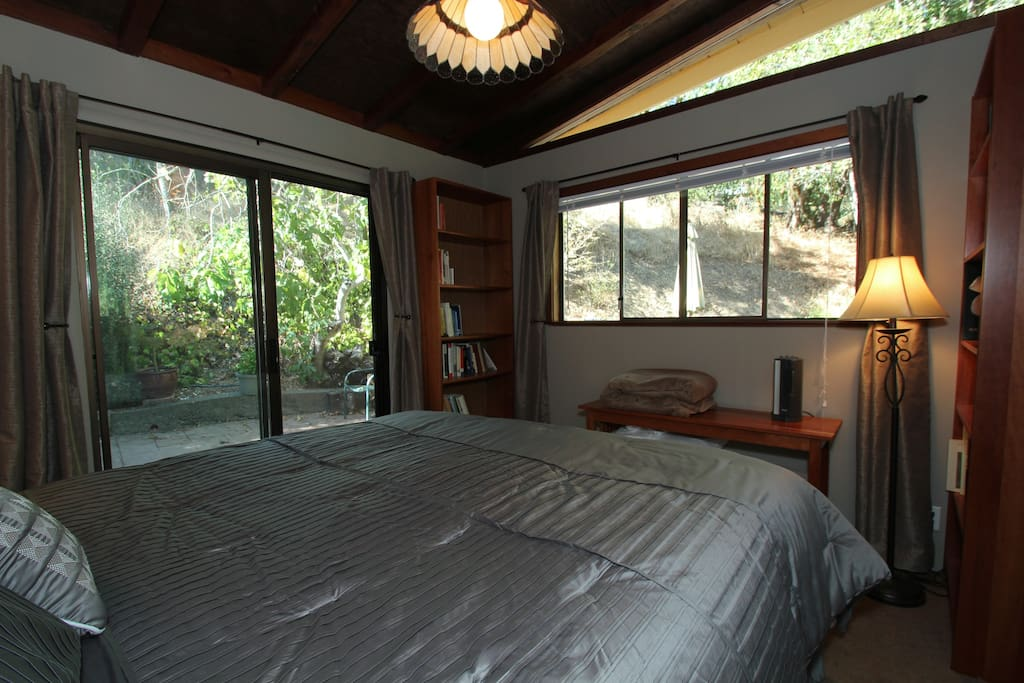 King bed - sliding glass door to small patio – double windows looking out to trees and large patio.
