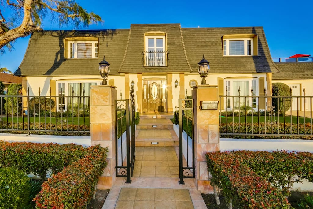 Styled like a French Manor house, ornate wrought iron fence surrounds entire front.