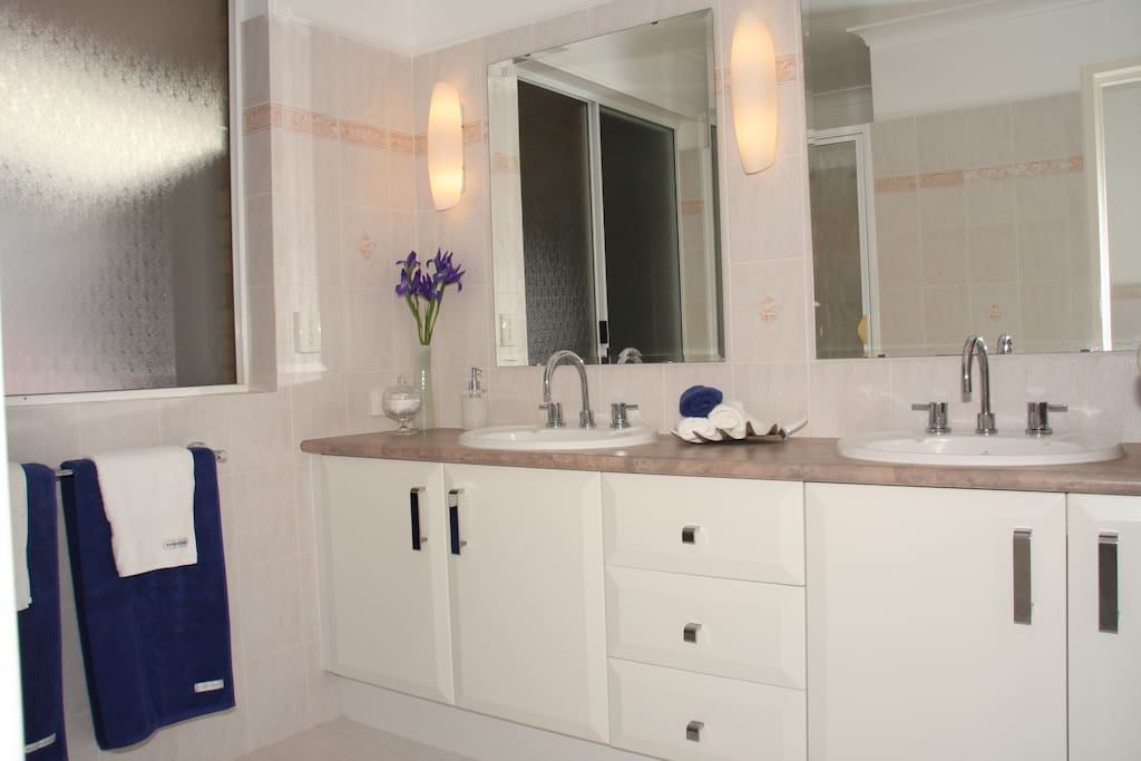Large bathroom with double vanity, luxuriously soft towels, own shower, own toilet, weighing scales, soaps, shampoo, conditioner, hairdryer, hair straightener, make up mirror + more