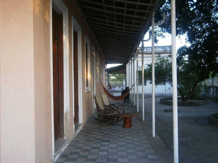 lateral da casa, mostrando casa/quarto anexo que possui  1 cama de solteiro e um banheiro.