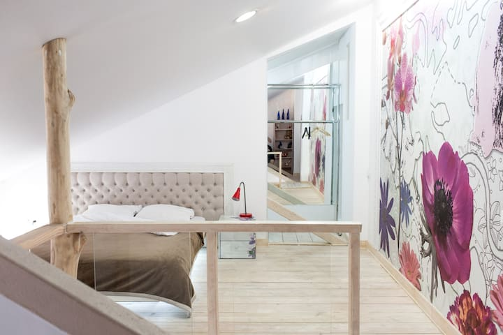 Спальная комната. Мансардный этаж с большой кроватью с дополнительным освещением
