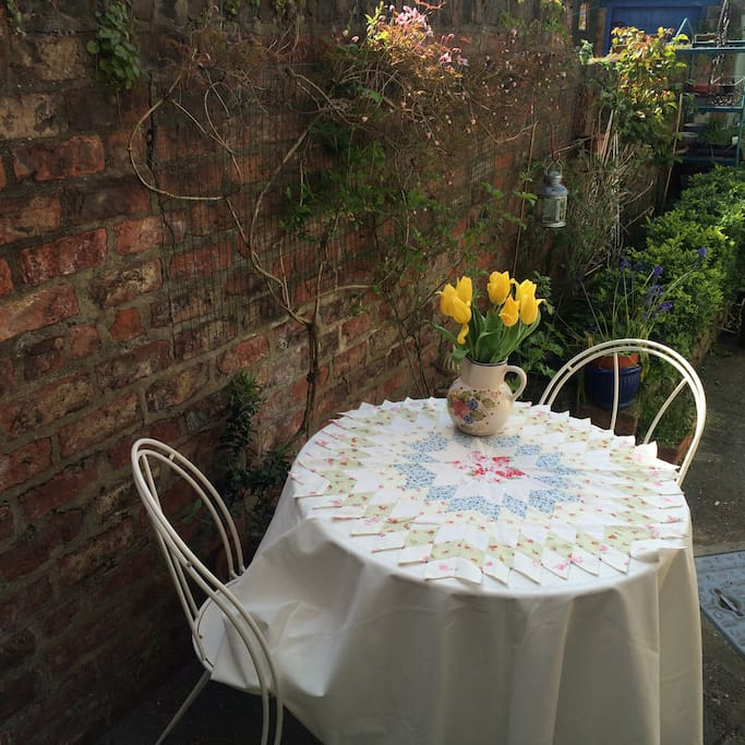 Relax in our sunny  courtyard - a tablecloth and cushions are provided as the table is a little 'rustic'! There are flowers in our garden for you to enjoy, but the flowers on the table are for illustrative purposes only ; )