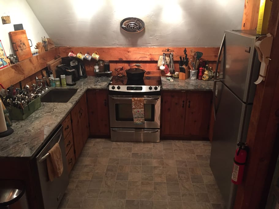 Fully equipped kitchen, with dishwasher, oven, fridge, microwave and granite countertops.