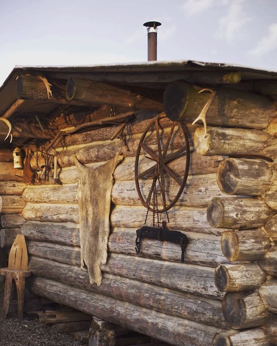 Round log logcabin decorated with authentic skins, antlers and rustic tools.