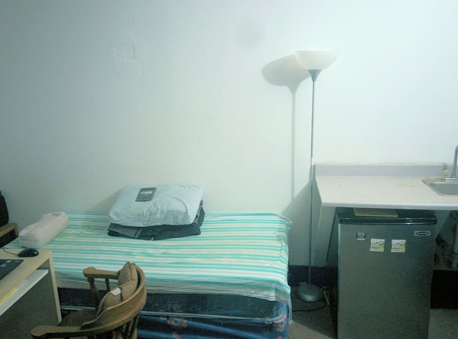 Very simple studio room with single bed refridgerator, water, heater microven.