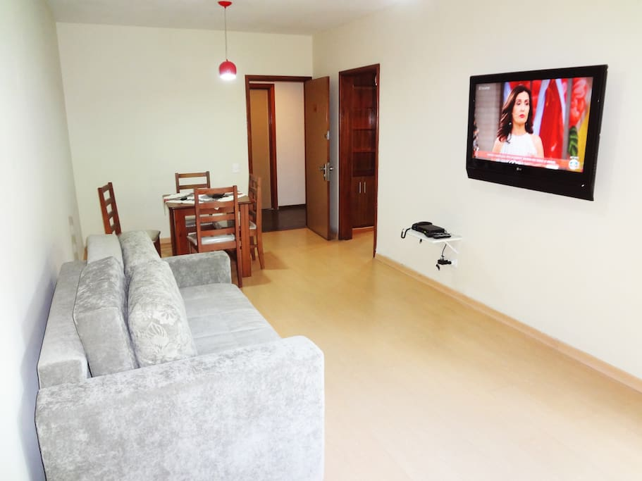 A spacious living room with a huge cable TV and an ar conditioning