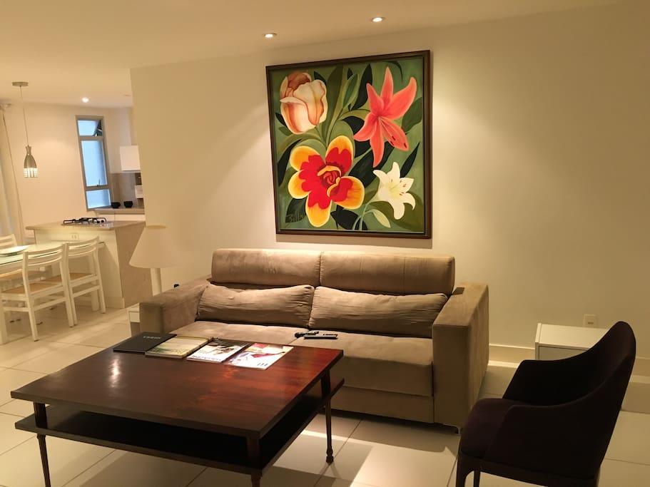 Sala com sofá reclinado, poltrona, telefone e tv a cabo.