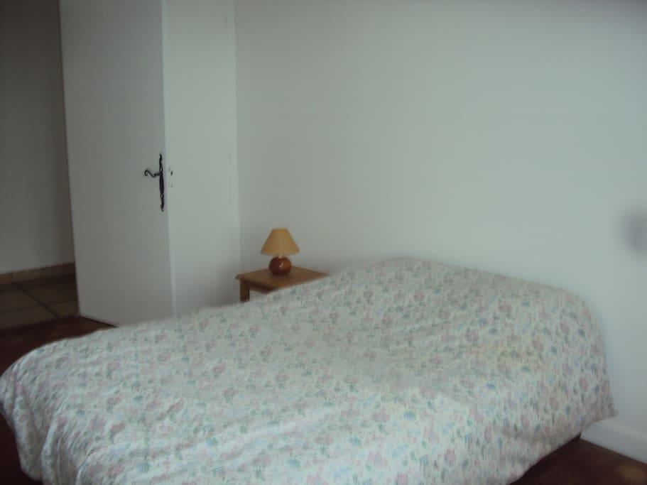 Une chambre avec un  lit  deux places et un lit à une place orientée est.