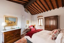 Impressive original beams in the bedroom rise high above the bed.