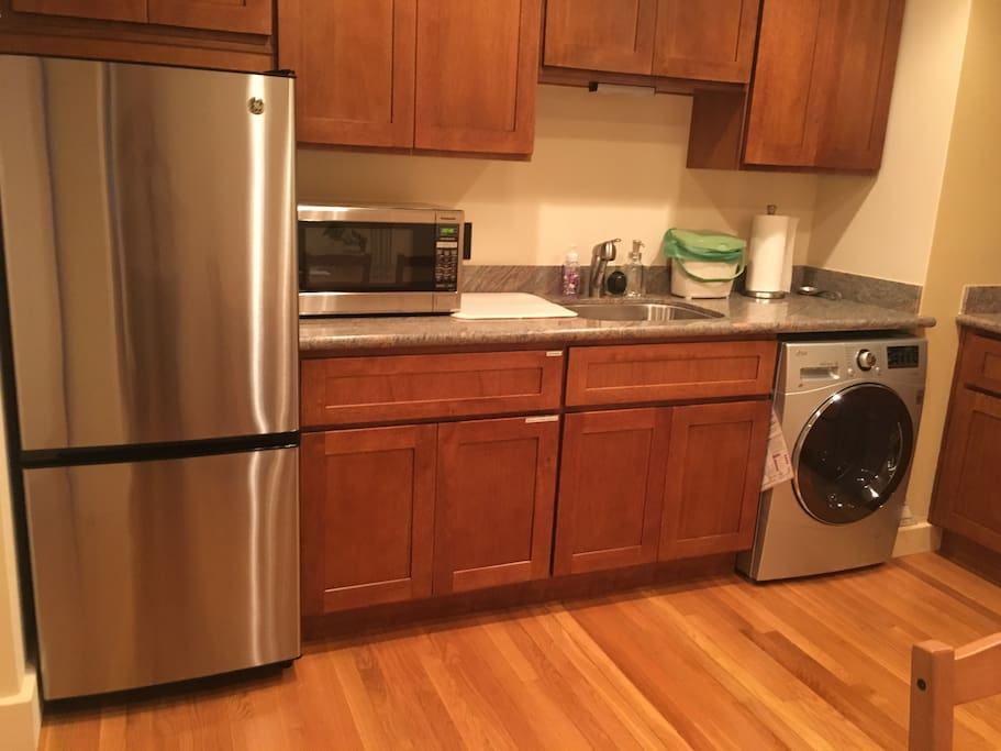 Kitchen - with wood cabinets, granite counter tops, washer/dryer combo and microwave.  Fully stocked with cups, plates, utensils, and cooking gadgets.