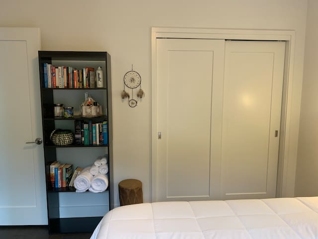 Bookshelf containing towels, additional toiletries, snacks, and books for your use during your stay.