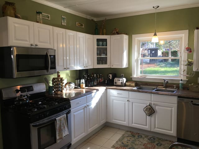 Kitchen with full amenities, including refrigerator, freezer, stove, microwave, spices, oils, coffee, and more.