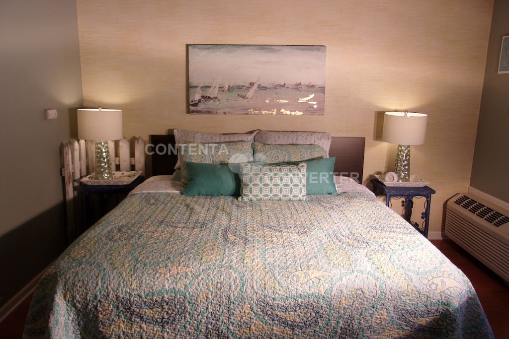 Newly remodeled bedroom with hardwood flooring, designer rugs, oil painting and sumptuous coastal bedding.