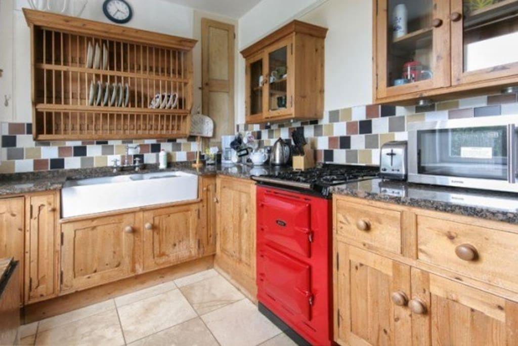 Farmhouse kitchen with Electric AGA oven and gas hob, fridge freezer, dishwasher, belfast sink