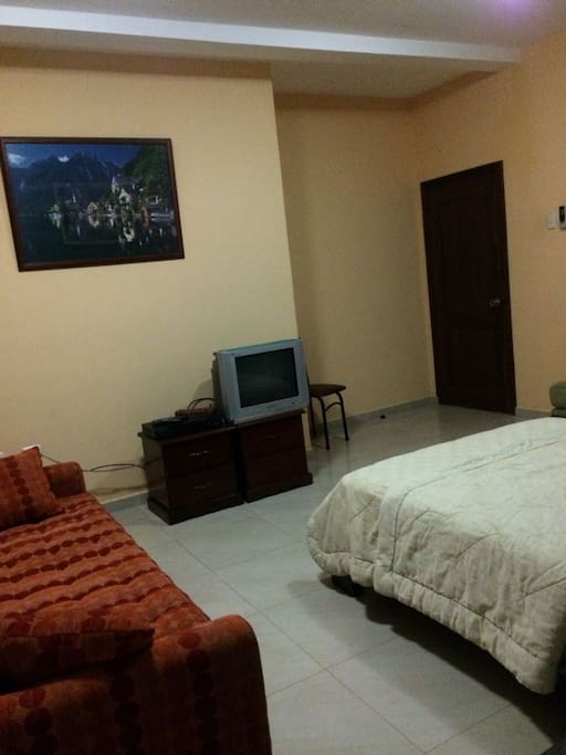 Vista de la puerta de entrada, TV y sofá desde puerta del baño.