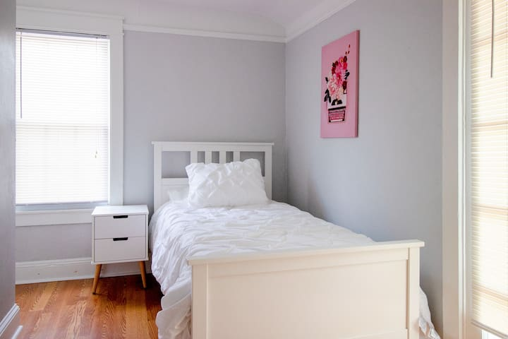 The second bedroom includes a twin size bed and a nightstand.