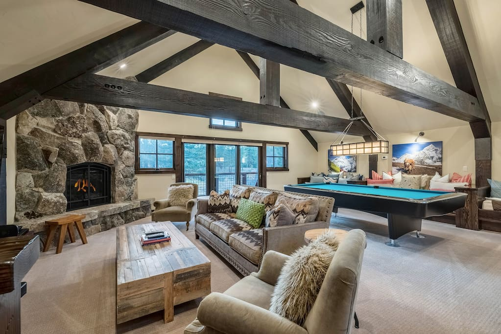 The upstairs rec room includes a pool table and couch seating beneath exposed beams.