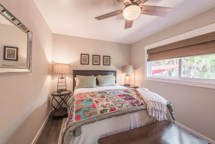The 2nd bedroom is outfitted with a queen bed and an antique armchair.