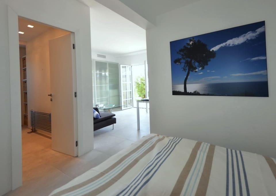 Blick von Schlafecke ins Wohnzimmer mit Ausgang zur Terrasse, Bad links