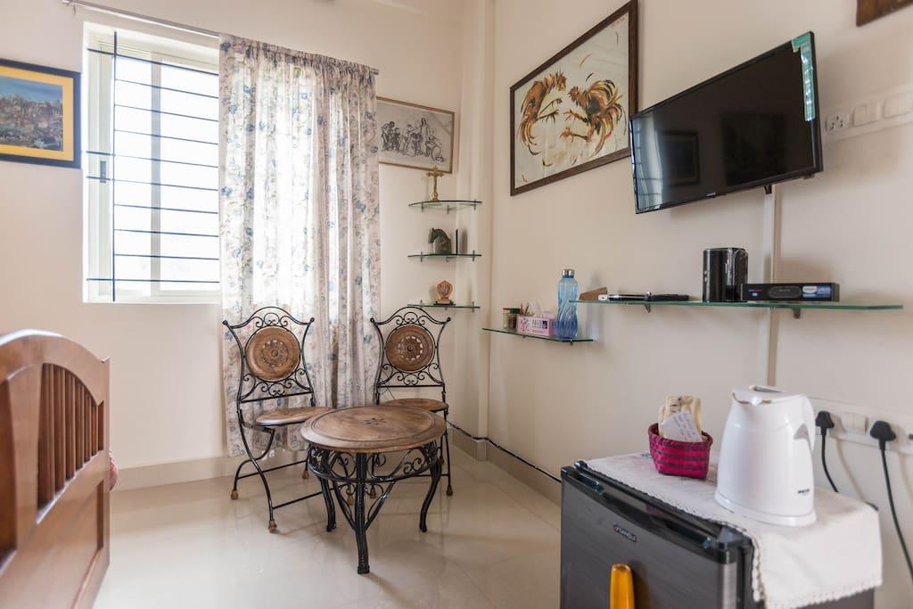 ...Enterance area showing some amenities like Mini Fridge, TV, Wi Fi & colourful Paintings