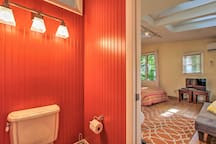 Bright red walls make up the bathroom.