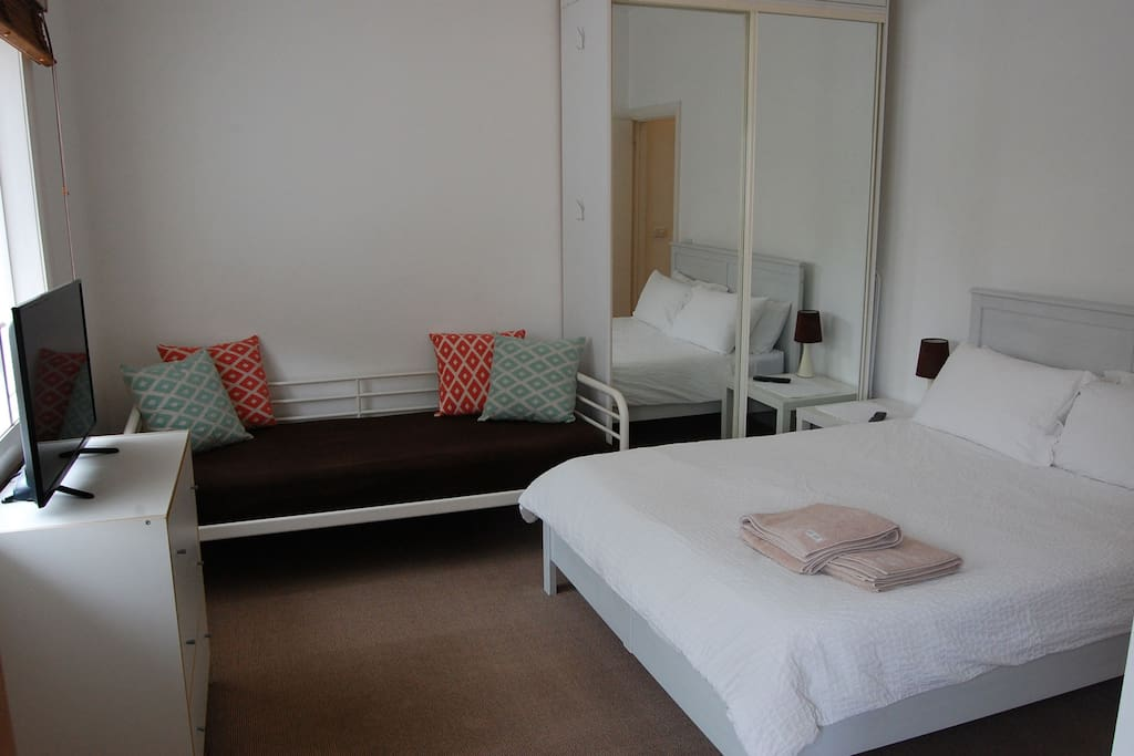 Spacious Main bedroom with spare day bed and plenty of cupboard storage.