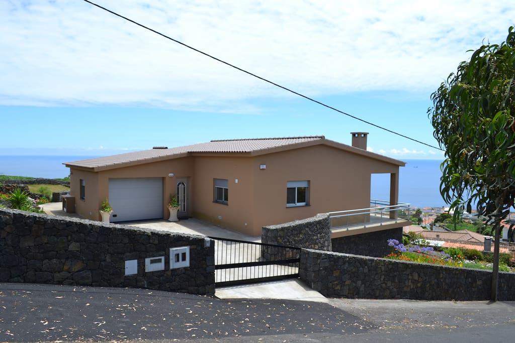 Casa vista de outro panorama, garagem, mar e jardim