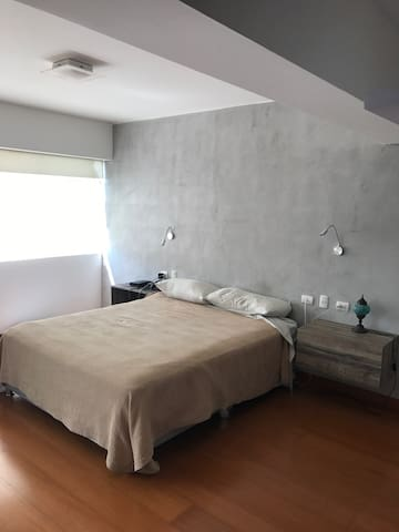 Bedroom with queen-size bed and night stands, high speed wifi, landline phone and wall-mounted reading lamps